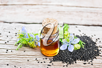 Nigella sativa oil in a bottle, seeds and twigs of black caraway seeds with blue flowers and green leaves on a background of an old wooden board