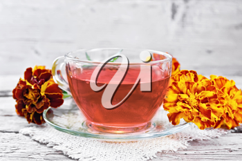 Marigold herbal tea in a glass cup and saucer on a napkin of sackcloth, fresh flowers on wooden board background