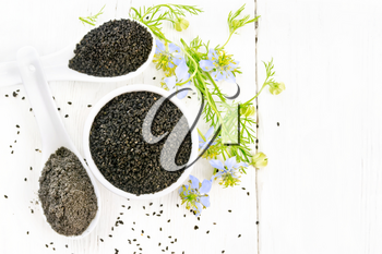 Black cumin seeds in a bowl, flour and seeds in spoons, kalingi sprigs with blue flowers and green leaves on a wooden board background from above
