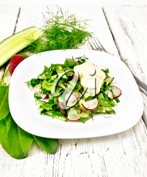 Salad of radish, cucumber, sorrel and greens, dressed with mayonnaise in a plate on the background of wooden board