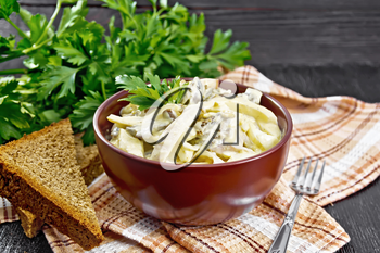 Salad with squid, egg and mushrooms in a bowl on a napkin, bread, a fork and parsley on wooden board background
