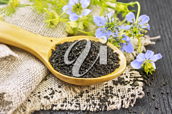 Black cumin seeds in a spoon on sacking, kalingi twigs with blue flowers and green leaves on a dark wooden board background