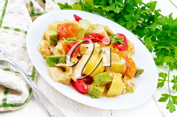 Vegetable ragout with zucchini, cabbage, potatoes, tomatoes and bell peppers in creamy sauce in plate, kitchen towel, parsley and a fork on wooden board background