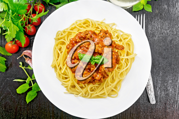 Spaghetti pasta with Bolognese sauce of minced meat, tomato juice, garlic, wine and spices in a plate, vegetable oil, spicy herb on a wooden board background from above