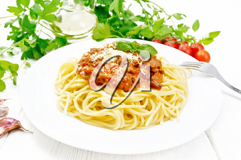 Spaghetti pasta with Bolognese sauce of minced meat, tomato juice, garlic, wine and spices with cheese and fork in a plate, vegetable oil, spicy herb on a light wooden board background
