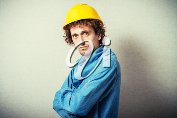 Curly man in a yellow hard hat. On a gray background.