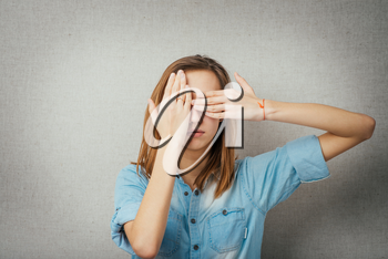 woman covers her face. isolated on gray background