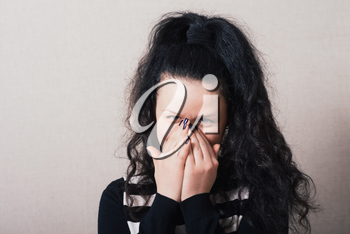 Woman laughing covering his face. Gray background