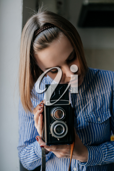 Portrait of a beautiful and attractive young woman holding a camera