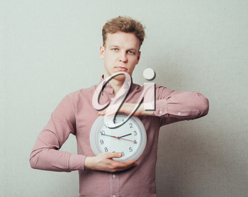 young man holding a clock in hand