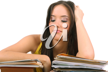Stressed young woman sitting at a table among books and papers on a white background