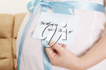 Pregnant belly with a light blue ribbon and a tag saying do not open until