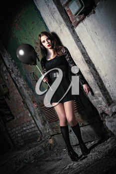 A strange young girl holding black balloon