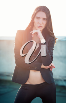 Outdoor fashion shot: a gorgeous beautiful young woman in pants, jacket and bra
