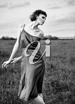 Outdoor fashion shot: beautiful sad girl in the field. Portrait of pretty young woman in dress. Black and white. Film grain effect
