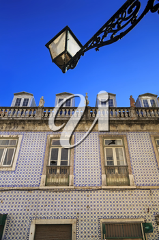 Blue portuguese tiles on house wall with cracks and latnern in the sky