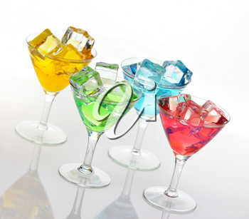 glasses of colorful drinks with ice cubes