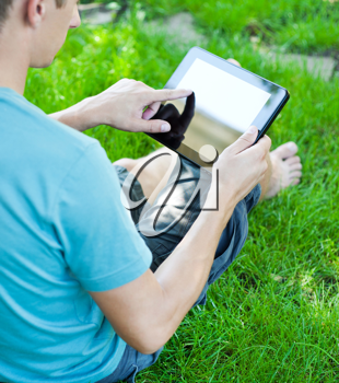 A young man uses tablet computer relaxing in green grass