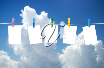 Blank photos hanging on a clothesline, blue sky on background