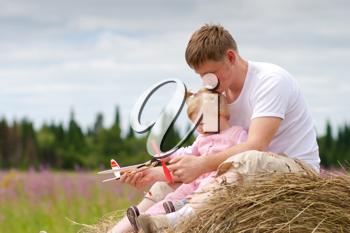 Royalty Free Photo of a Father and Daughter on a Haystack
