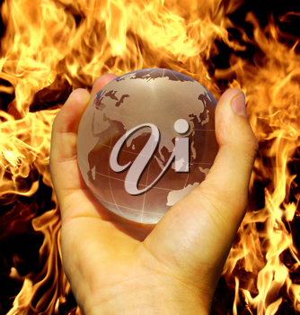 Royalty Free Photo of a Person Holding a Globe by Fire