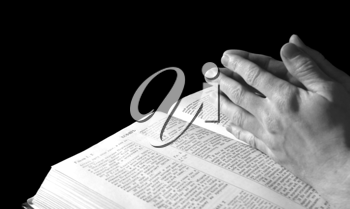 Royalty Free Photo of Hands Clasped Over the Bible