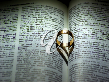 ring and heart shaped shadow over a Bible