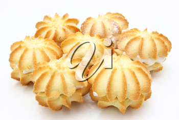 Yellow cookies with a white stuffing lie on a white background in the form of a circle