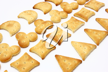 Salty crackers of the various geometrical form lie on a white background