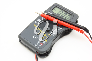Multimeter of black color with a red and black wire on a white background