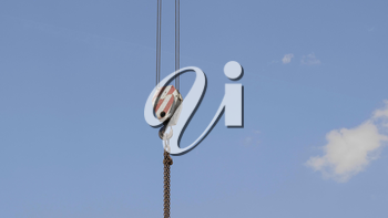 Crane hook with red and white stripes hanging, blue sky in background.