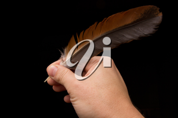 Hand writting with feather isolated on black background