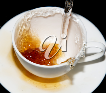 tea being poured into a saucer with splashes on a black background