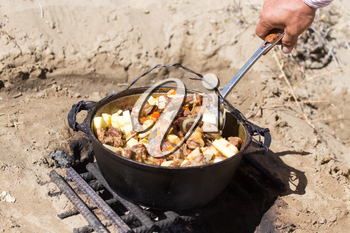 meat with potatoes in a cauldron on fire