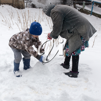 a boy with his grandmother playing in the snow .