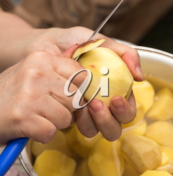 The cook cleans the potatoes with a knife .