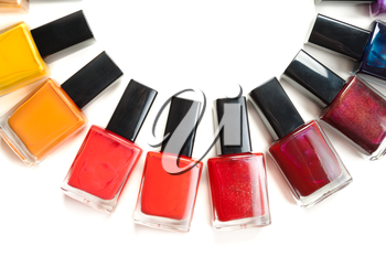 Coloured nail polish packed in a semicircle on a white background