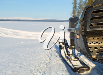 fragment of a snowmobile against a winter landscape