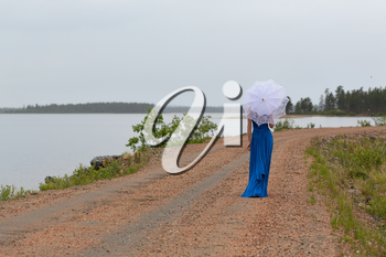 Slim girl in a dress with an umbrella in a forest on a country road