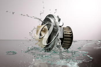 Auto parts, engine cooling pump in spurts of water on a light gradient background