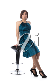 Beauty woman on a bar chair in a blue dress in the studio, isolate on white.