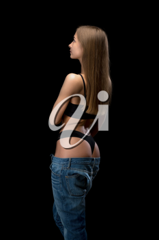 Beauty girl in jeans from behind. Isolate on a black background.