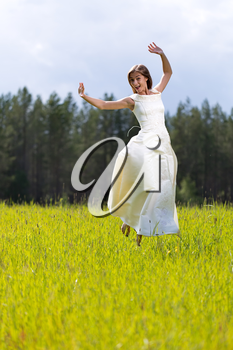 woman in a wedding dress jumping in a field with a smile