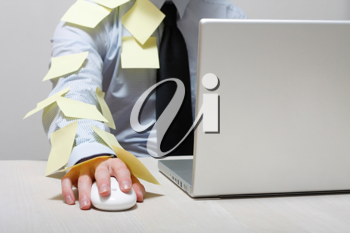 Royalty Free Photo of a Man Covered in Yellow Notes by a Laptop