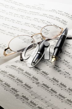 music charts with glasses and pen on top