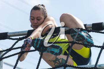 Royalty Free Photo of a Female Competitor Climbing Ropes