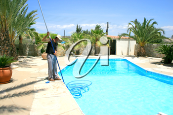 Royalty Free Photo of a Man Cleaning a Swimming Pool