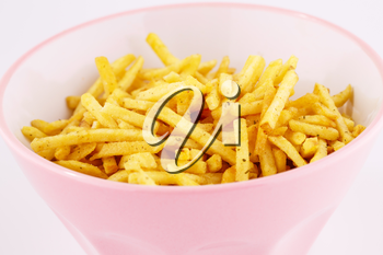 Potato chips in pink bowl isolated on gray background.