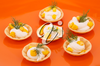 Cheese cream, sweet corn and dill in pastries in orange plate.