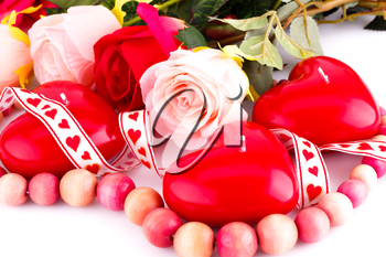 Red heart candles, wooden necklace, ribbon and roses on white background.